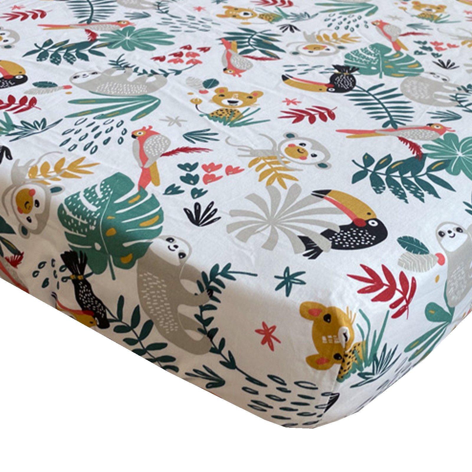 BINK Bedding hoeslaken Zoë 60x120 cm met kleurrijke toekans, luiaards, tijgers, apen, pagegaaien en bladeren op een witte ondergrond.