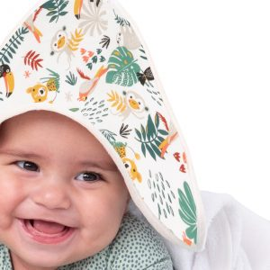 Baby met BINK Bedding badcape Zoë. Een vrolijk dieren dessin met kleurrijke toekans, luiaards, tijgers, apen, pagegaaien en bladeren op een witte ondergrond.