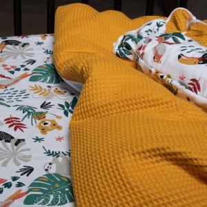 BINK Bedding hoeslaken Zoë met kleurrijke toekans, luiaards, tijgers, apen, pagegaaien en bladeren op een witte ondergrond in combinatie met een dekbedovertrek Pique wafel oker en kruikenzak Zoë.